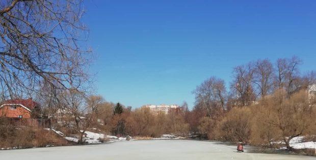 Дом 12 по улице Семёна Гордого выглядывает из-за деревьев около каскада прудов, тает лёд, но рыбаки сидят до последнего ТиНАО ЖК Ново-Никольское Первомайское Новая Москва